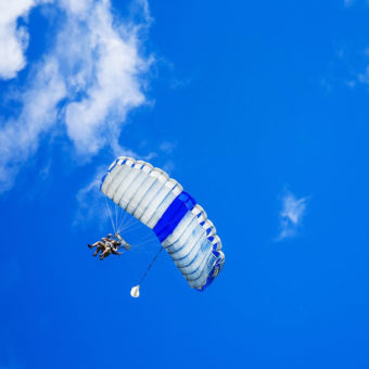 Skydivers with a parachute